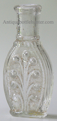 An early colorless beaded plume with opposite side featuring a beaded oval space, likely used for a label. A pontil mark is on the base. Height, 2 - 7/8 in. Width, 1 - 3/8 in. --- AntiqueBottleHunter.com