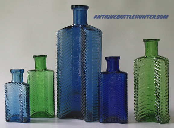 A light steel blue (2 - 7/8 in.), light green (3 - 1/2 in.), steel blue (6 - 3/8 in.), dark blue (3 - 1/2 in.), and finally a yellow green (4 - 1/2 in.) set of KU-21s --- AntiqueBottleHunter.com