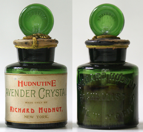 A light yellow green cylinder shaped bottle embossed: RICHARD HUDNUT / (Fleur de lis) CHEMIST (Fleur de lis) / NEW YORK. Stopper: HUDNUTINE in an arc over a H. Label reads as shown in picture. It still contains it's contents, is sealed with wax and has a green string at stopper. The base has a golden label with trade mark name and large bird. Height w/out stopper, 2 - 3/4 in. Width, 2 in. --- AntiqueBottleHunter.com