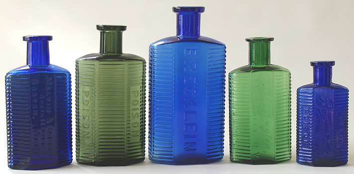 COLLECTION PHOTO OF SOME IRREGULAR HEXAGON POISONS - Melvin and Badger with label, Olive green KI-1, Brecklein, Yellow green Hetherington, and a Bowman's Drug Store.