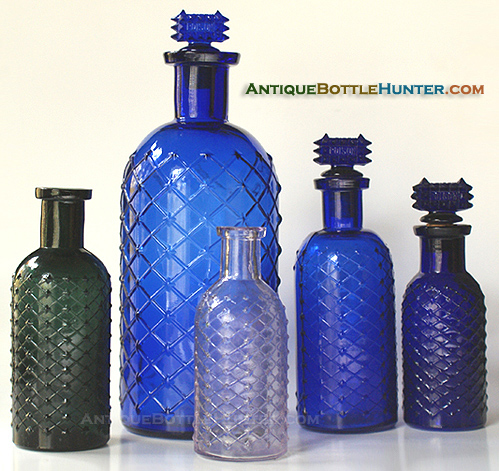 A group photo of lattice and diamond cylinder poisons, including a teal green, a light amethyst (SCA) and some blues --- Antiquebottlehunter.com