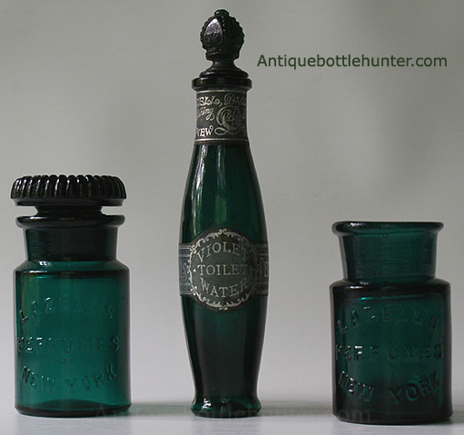 Three LAZELL'S bottles in various shades of teal. Two salts bottles embossed the same, flanking a toilet water. The left one has more of a shoulder to it and an embossed (script monogram) ground stopper. The middle bottle is embossed on the opposite side: LAZELL'S / NEW YORK /PERFUMES. It has two black and silver labels. One states: Violet Toilet Water... and the other mentions: Lazell, Dalley & Co. We're not sure if the fancy stopper is original, but it looks great. The far right variant has a crude lip and the shoulder is at a sharper angle. --- AntiqueBottleHunter.com