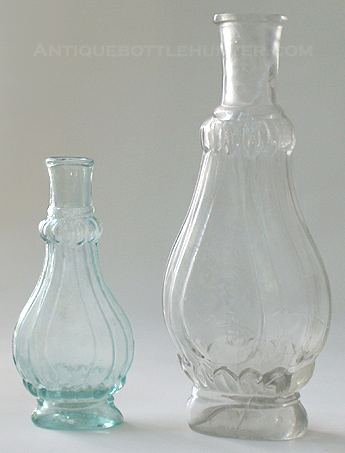 An aquamarine and taller colorless 'Fluted' cologne. (4 in. and 6 in.) --- AntiqueBottleHunter.com